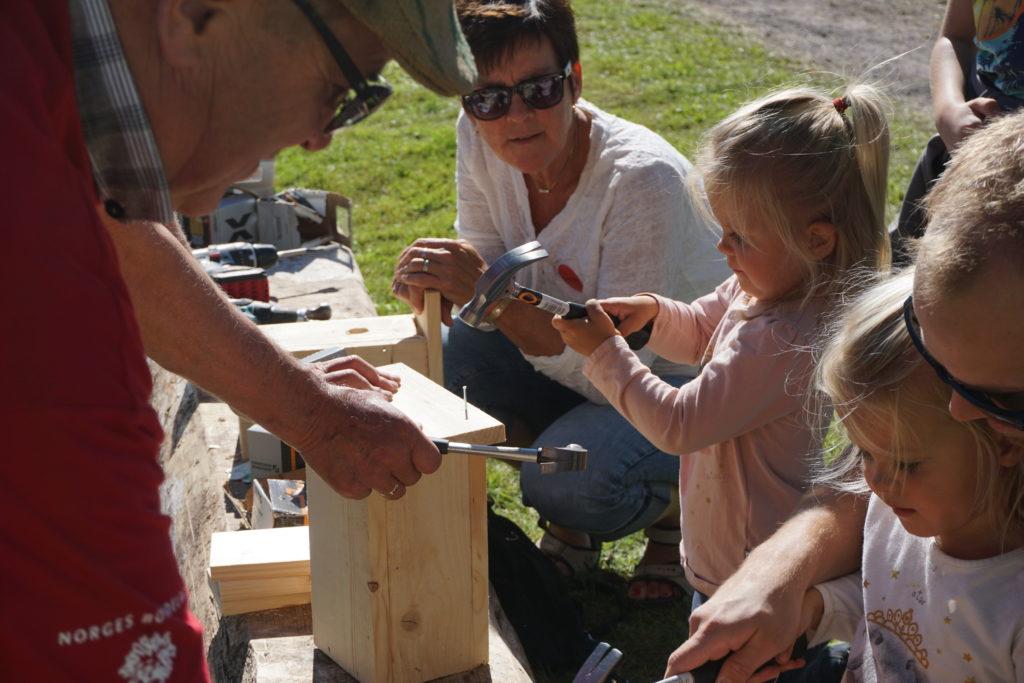 Otilie Ommedal snekrer fuglekasse ved siden av søsteren Olivia Ommedal og farmor